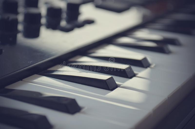 Piano or electone midi keyboard, electronic musical synthesizer white and black key. Vintage effect, instagram filter. Style. Close up stock photography