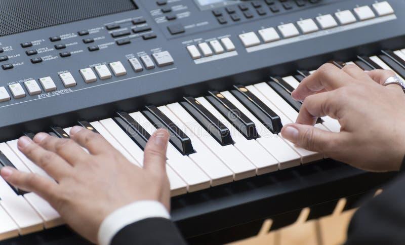 Piano eletrônico de Palying das mãos fotografia de stock