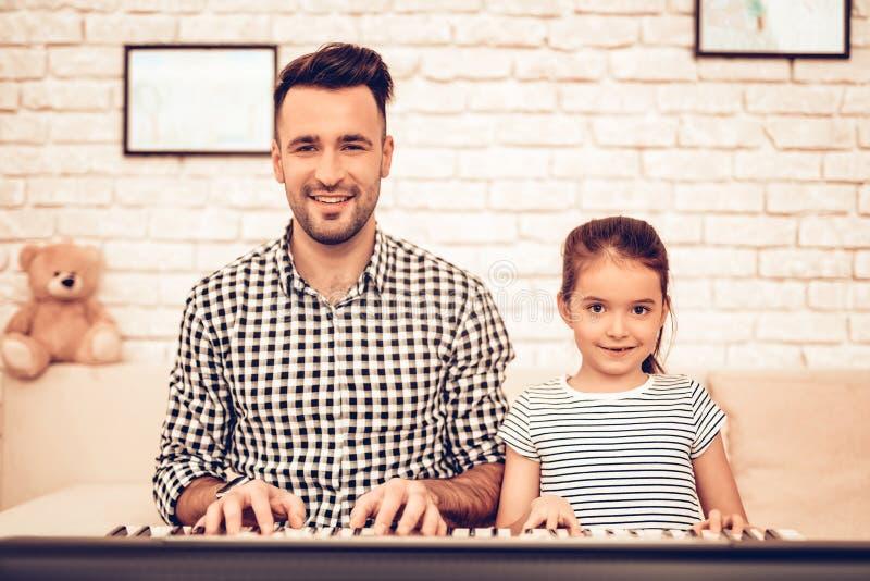 piano för bakgrundsgitarrmusik FaderAnd Daughter On soffa Spendera tid tillsammans dagfader s royaltyfri fotografi