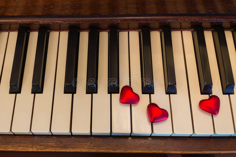Piano Key Hearts. Red heart shapes rest on the keys of an old upright piano stock photos