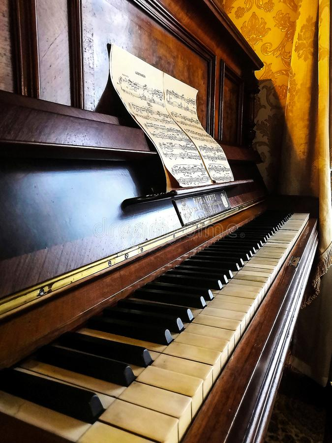 Piano keyboard background with selective focus. Warm color toned image. Open brown piano with notes stock images