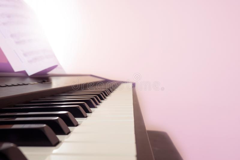Piano keyboard with note. Pink color filter with light effect. C. Opy space. Classical music instrument. Art and abstract background stock photos