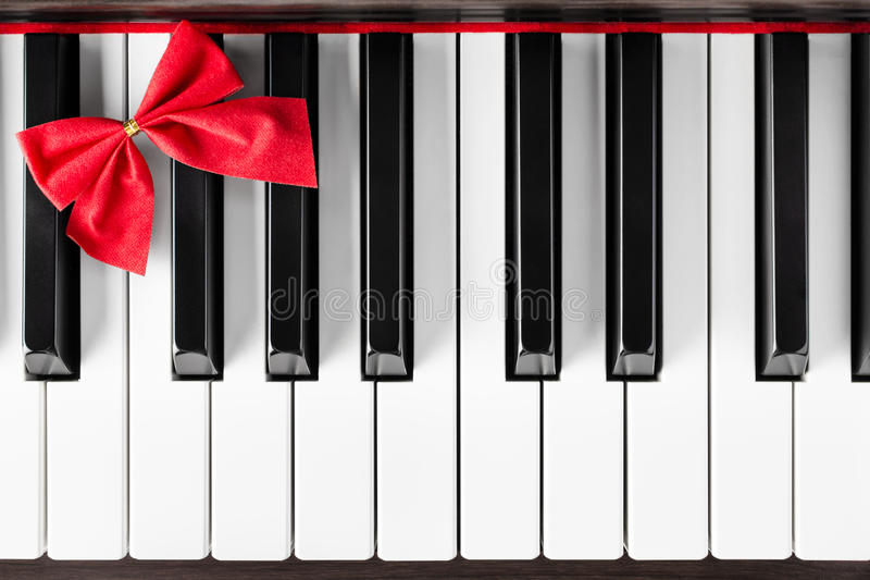 Piano keyboard with red ribbon. A closeup shot of piano keyboard with red ribbon in left corner - bird's eye view stock photo