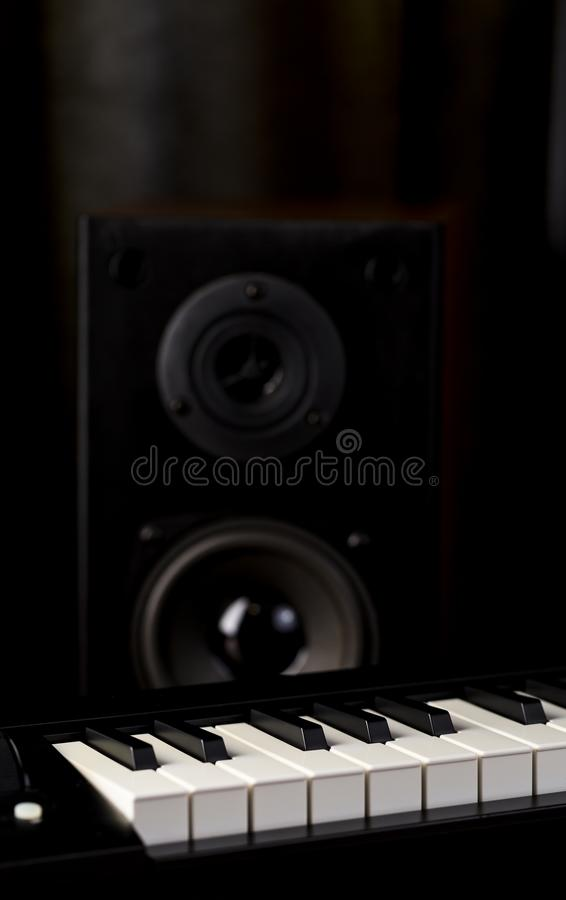 Piano keys and audio speaker closeup on dark background. Vertical composition stock image