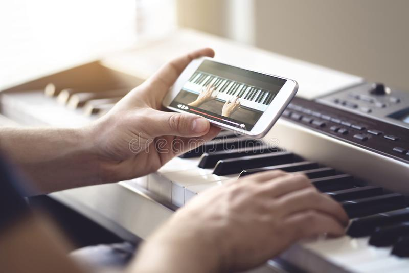 Piano lesson online. Man watching video tutorial with mobile phone and practising playing. Person learning to play an instrument. Piano lesson online. Man royalty free stock image