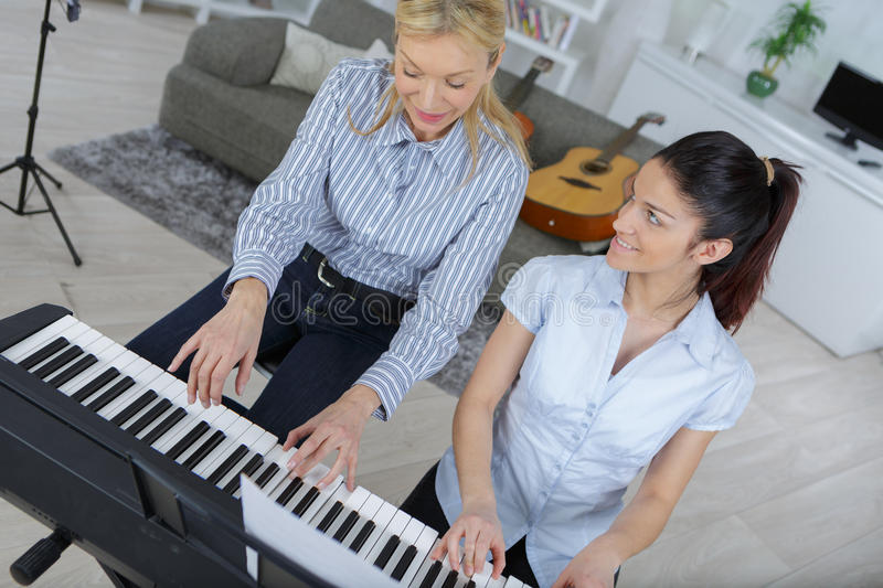 Piano lessons at music school teacher and student stock photos