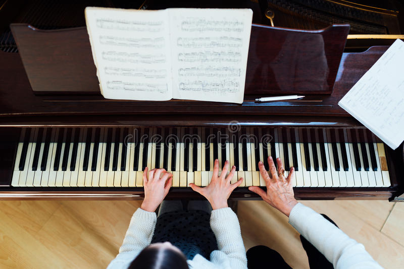 Piano lessons at a music school, teacher and student royalty free stock images