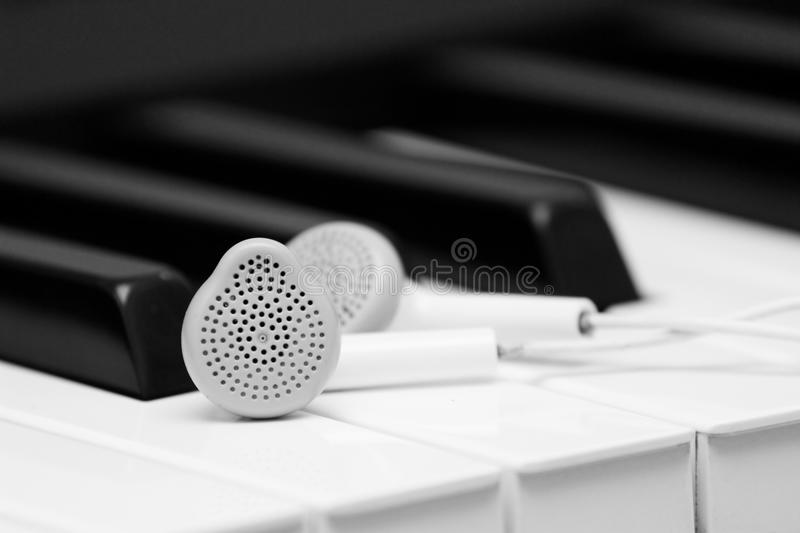 Piano music and earphones background. Instrumental piano music illustrated by a photo with grand piano keys and a pair of earphones royalty free stock photos