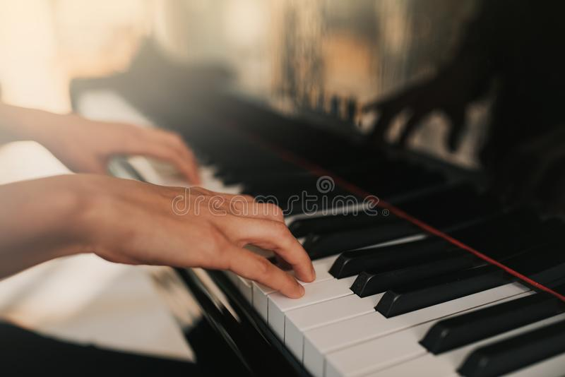 Piano music pianist hands playing. Musical instrument grand piano details with performer hand on white background stock photography