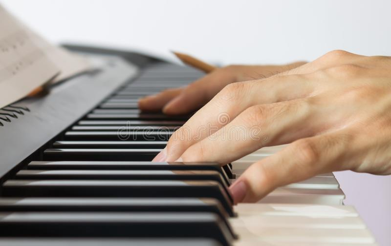 Piano Player Hand on Electric Piano with Sheet music royalty free stock photos