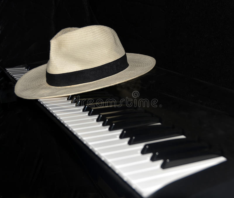 Piano Player Takes a Break - Panama Hat. Piano player takes a break leaving a Panama hat on the keys at night. Focus on hat royalty free stock image