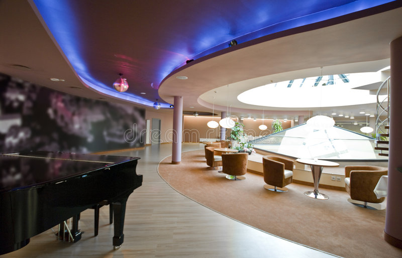 Piano in restaurant. Interior of a modern hotel, the restaurant with a classic piano in the foreground royalty free stock photography