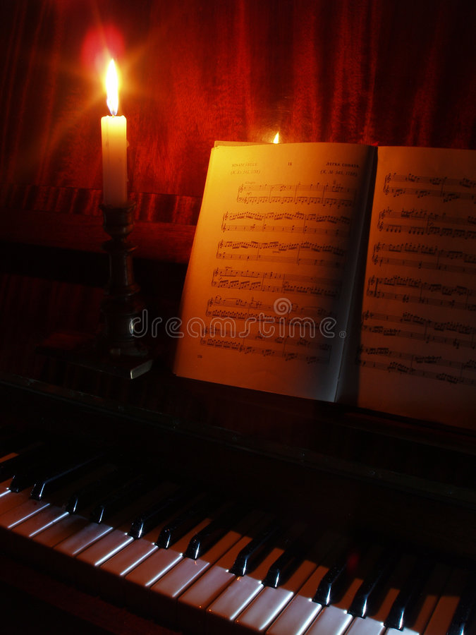 Piano and sheet music in the light of candle royalty free stock images