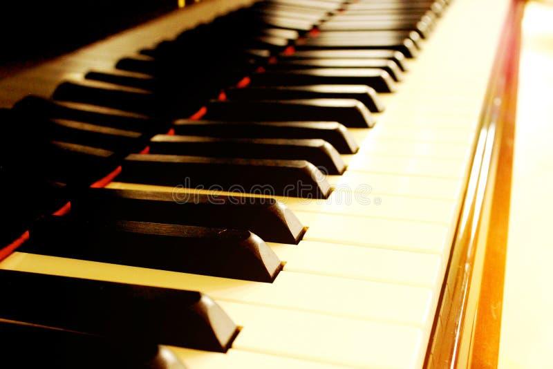 Piano touché par les faisceaux du soleil photographie stock libre de droits