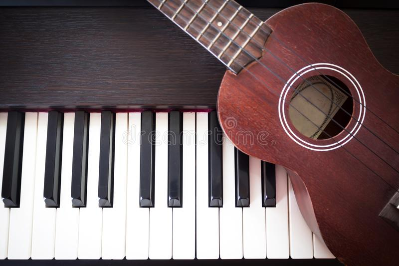 Piano with Ukulele. Art and Music background. Top view with dark vignette. Piano with Ukulele. Art and Music background. Two kind of music instruments. Top view royalty free stock photo