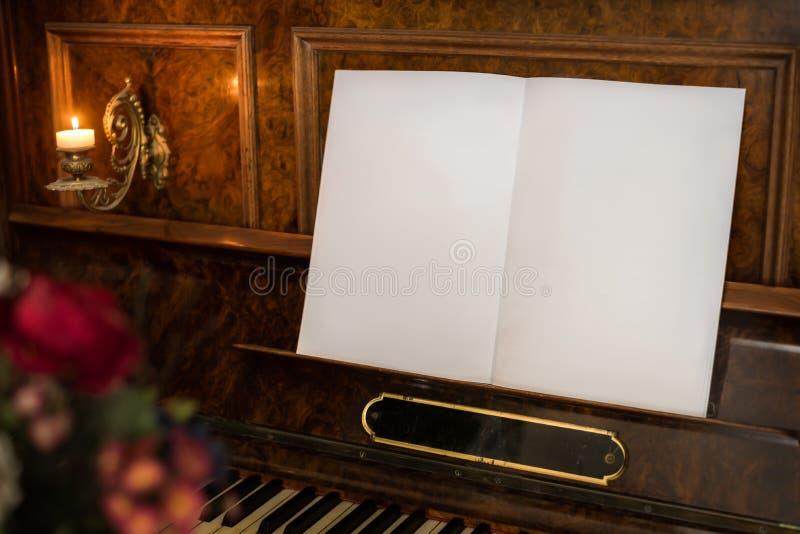 Piano viejo con el libro en blanco abierto con el espacio de la copia imagen de archivo libre de regalías
