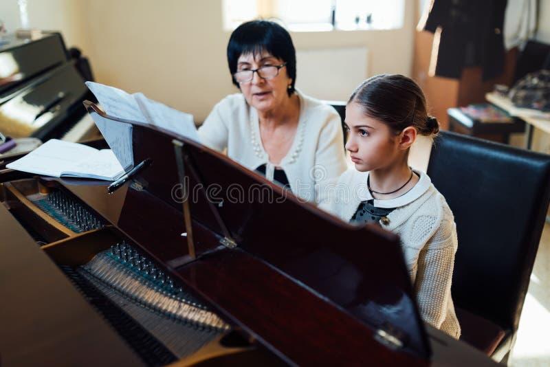 Pianolessen bij muziekschool, leraar en student stock fotografie