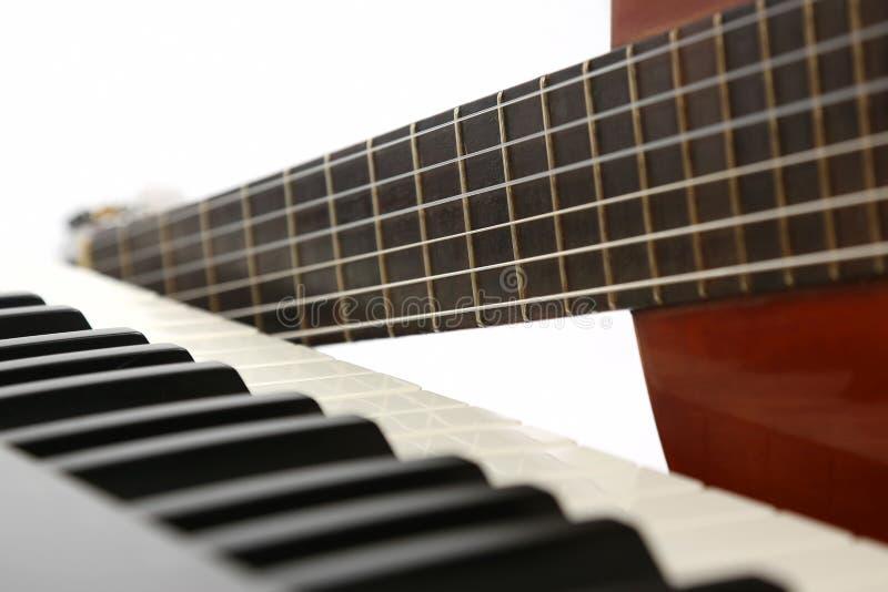 Pianosleutels en klassieke gitaar dichte omhooggaand op witte achtergrond royalty-vrije stock foto's