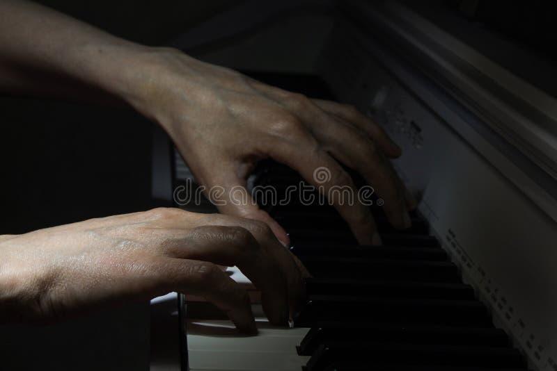 Pianosleutels en menselijk handenclose-up stock foto's