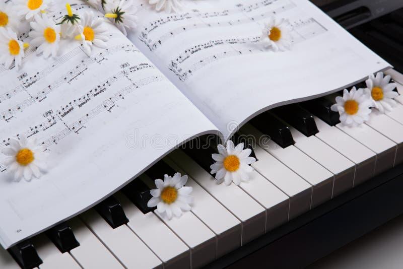 Pianotangenter och musikalisk bok och blomma arkivfoto