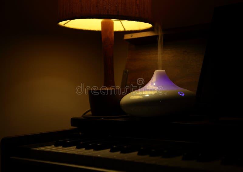 Pianotoetsenbord, schemerlamp, etherische oliespuitbus royalty-vrije stock foto's