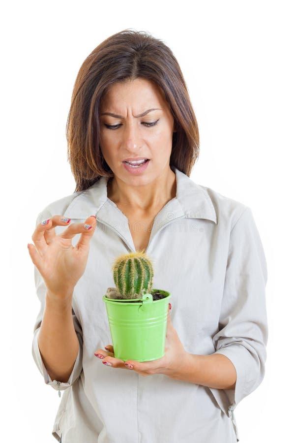 Pianta del cactus della tenuta della donna e pugnalato il suo dito con la f dolorosa fotografia stock