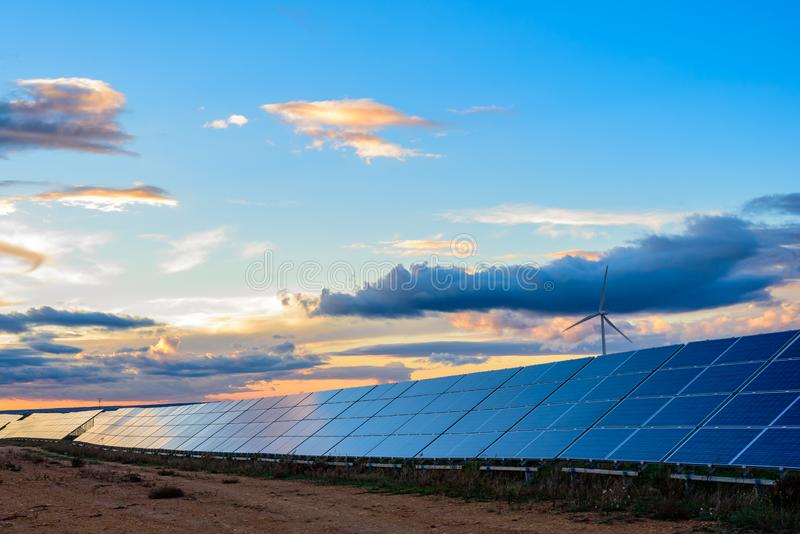 Pianta del vento e fotovoltaica al tramonto immagini stock