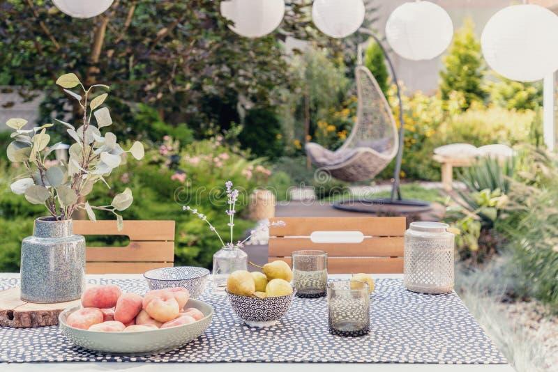 Pianta ed alimento sulla tavola nel giardino con la sedia d'attaccatura vaga nei precedenti immagini stock libere da diritti