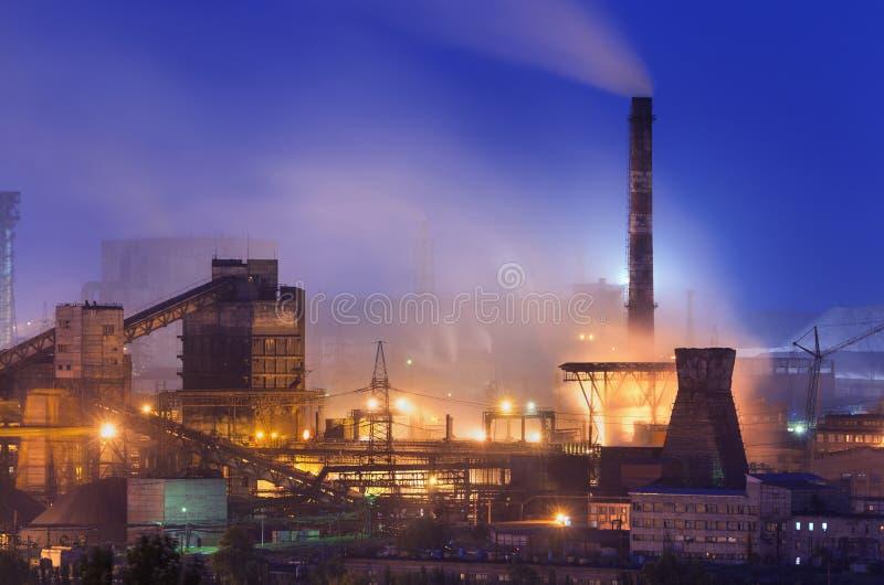 Pianta metallurgica alla notte Fabbrica d'acciaio con i fumaioli immagini stock libere da diritti