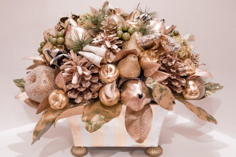 Piantatrice elegante di Natale degli ornamenti sbalorditivi dell'oro in un supporto che si siede su una tavola fotografie stock