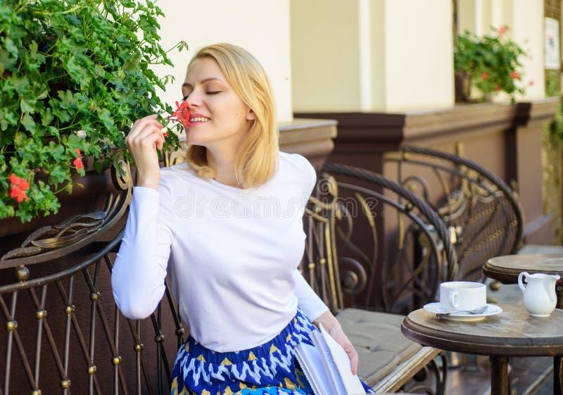 Piante come decorazione naturale La ragazza si siede l'aroma dei fiori di annusata del caffè La donna si siede il terrazzo del ca fotografia stock libera da diritti