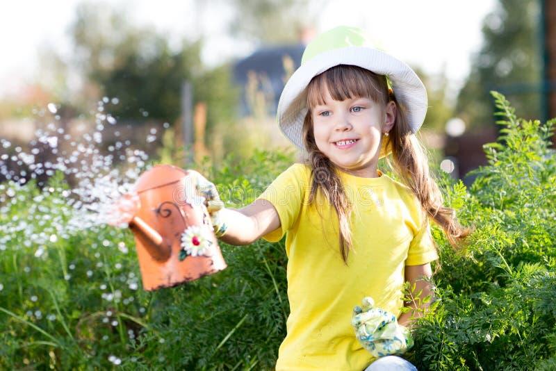 Piante di innaffiatura della bambina in un giardino fotografia stock