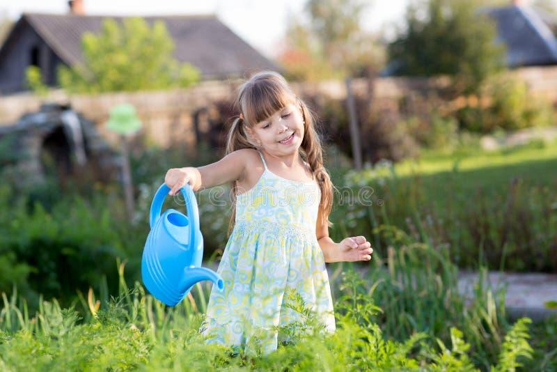 Piante di innaffiatura sveglie della bambina nel giardino fotografia stock libera da diritti