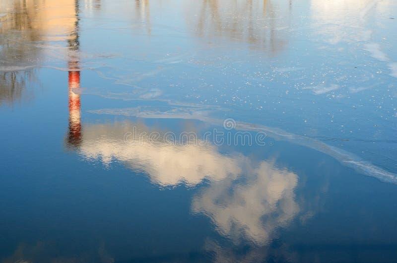 Pianti i tubi con fumo nella riflessione dell'acqua immagini stock