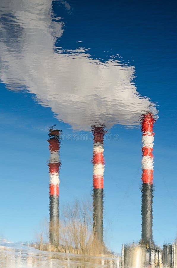 Pianti i tubi con fumo nella riflessione dell'acqua fotografie stock