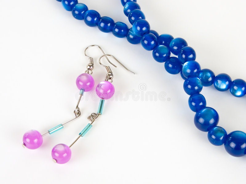 A piar of earrings and a pearl necklace. Against white background royalty free stock photos
