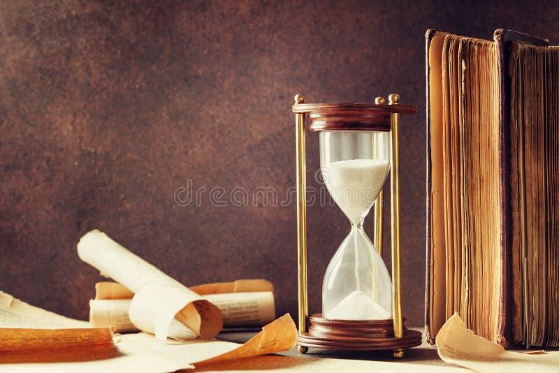 Piaska bieg przez starych rocznik książek i hourglass Czasu pastucha pojęcie obrazy royalty free