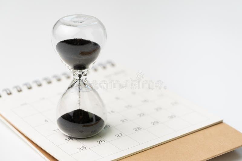 Piaska szkło lub godziny szkło na białym czystym desktop kalendarzu z wh obraz stock