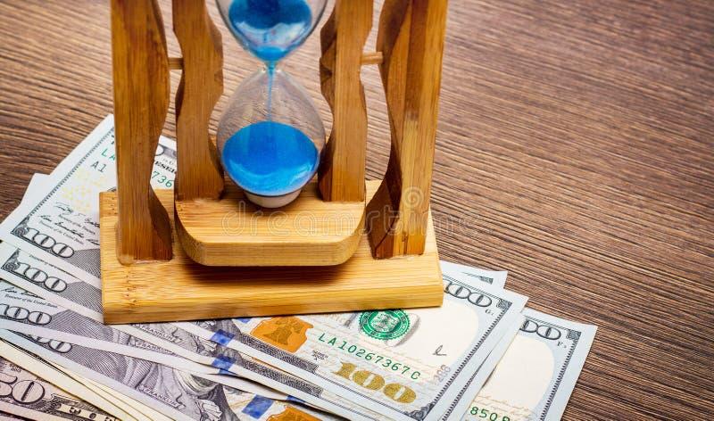 Piaska zegar na dolarowych rachunkach Czas zarabiać pieniądze Czas jest money_ obraz royalty free
