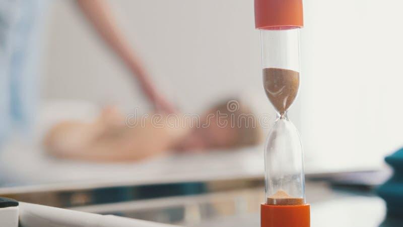 Piaska zegar w gabinecie tibetan medycyna - masuje dla młodej blondynki kobiety zdjęcia stock