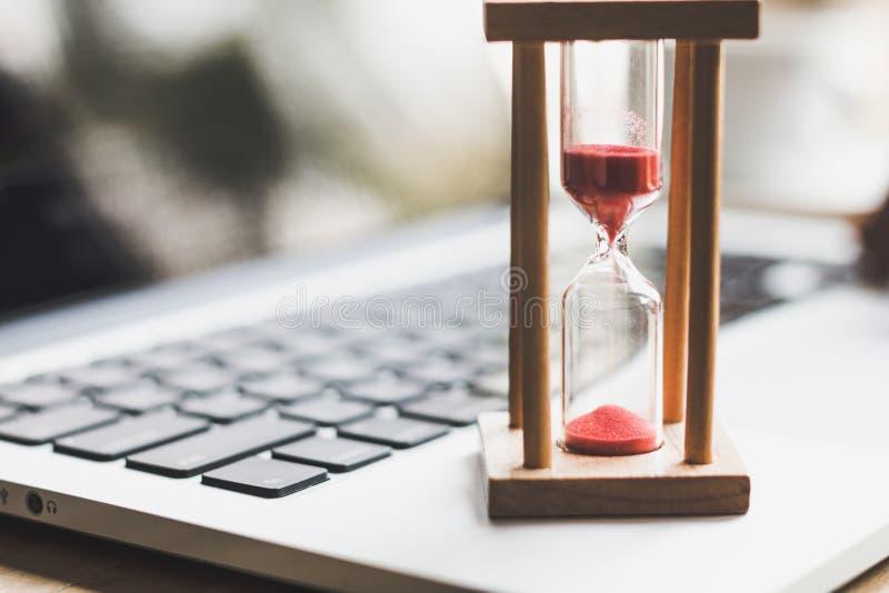 Piaska zegarowy zegar na laptopie Symbol czas obraz stock