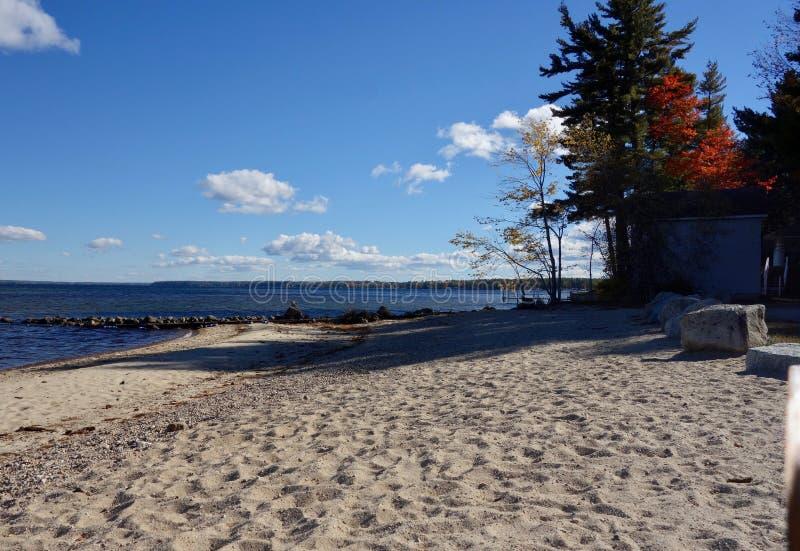 Piaskowata jezioro plaża z odciskami stopymi w piasku, lato zabawa, Sebago jezioro, Sebago, Maine obraz royalty free