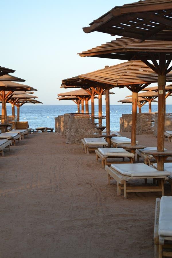 Piaskowata plaża blisko morza z drewnianym parasolem zdjęcia royalty free