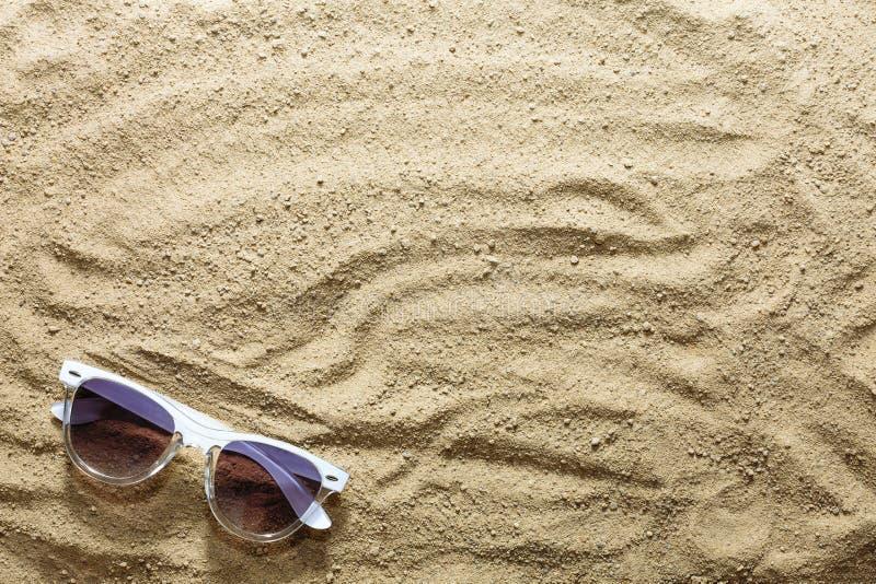 Piaskowata plaża i okulary przeciwsłoneczni na seashore lub oceanie beach tło Pojęcie: wakacje morze, podróż, wakacje zdjęcie royalty free