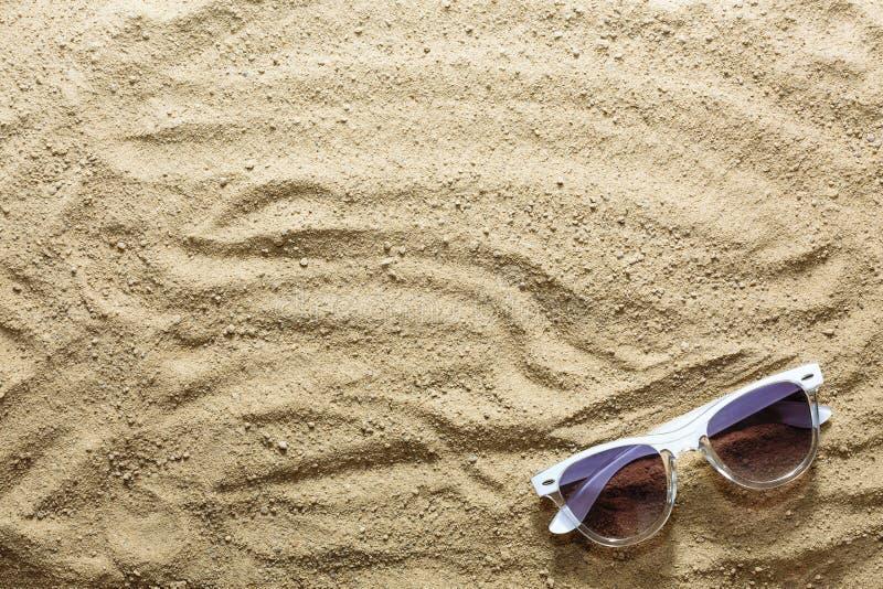 Piaskowata plaża i okulary przeciwsłoneczni na seashore lub oceanie beach tło Pojęcie: wakacje morze, podróż, wakacje zdjęcie stock