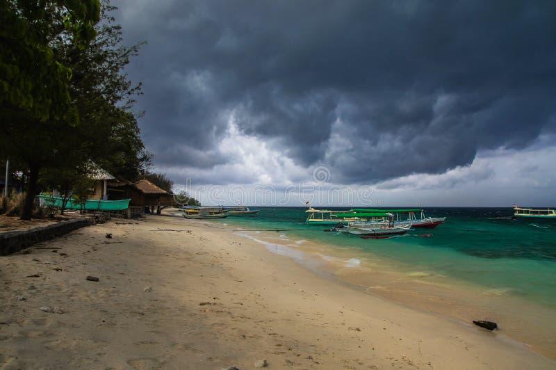 Piaskowata plaża z cumować Indonezyjskimi łodziami na tropikalnej wyspie Gil Meno Ciężkie powolne chmury wieszali nad plażą, a obraz royalty free