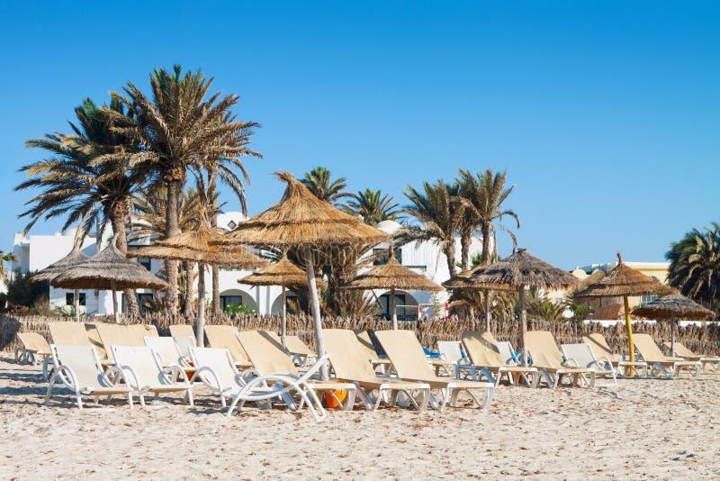 Piaskowata plaża z deckchairs i parasols zdjęcie stock