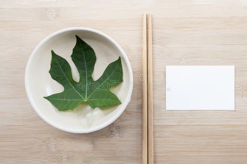 Piastra di ceramica con bacchette e carta imbottita di carta bianca sullo sfondo della tavola di legno con spazio di copia per il fotografie stock