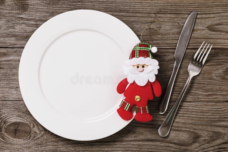 Piastra vuota e posate su una tavola di legno con spazio di copia Babbo Natale, un giocattolo di Natale morbido Sfondo alimentare immagine stock libera da diritti