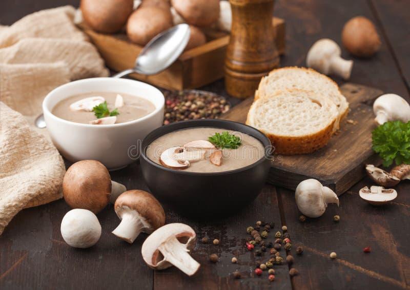 Piastre di ciotola in ceramica di castagno campione di funghi cremoso con cucchiaio, pepe e tessuto da cucina su fondo di legno s fotografie stock libere da diritti